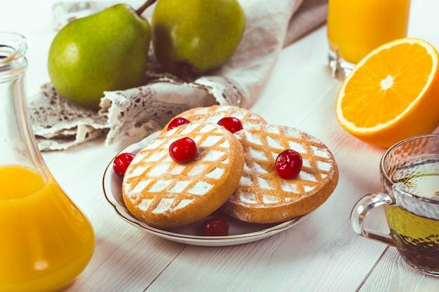 Ciasteczka na talerzu z jagodami i owocami na stole
