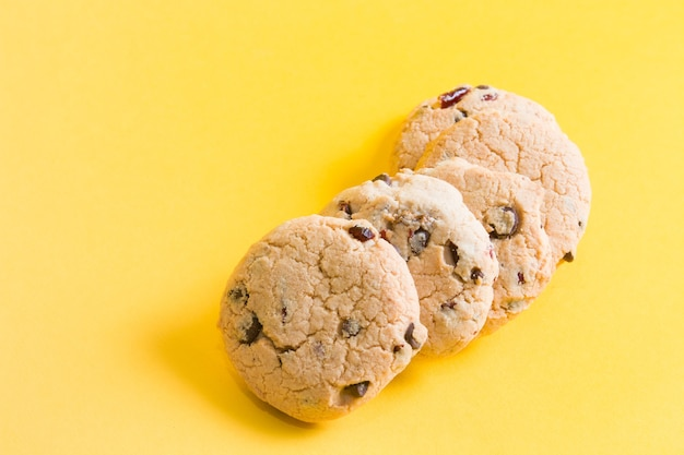 Ciasteczka na żółtej powierzchni, ciasteczka z kawałkami czekolady i borówkami
