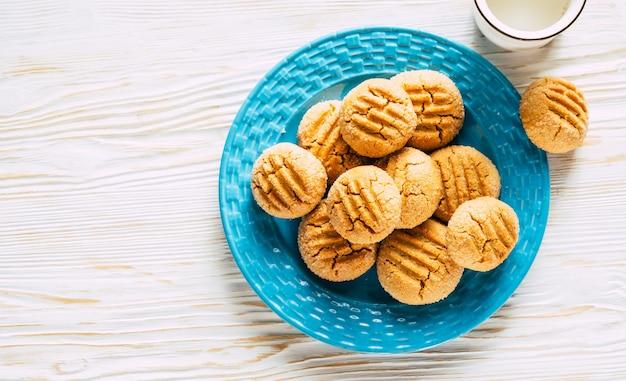 Ciasteczka orzechowe w niebieskim talerzu na białym drewnianym tle