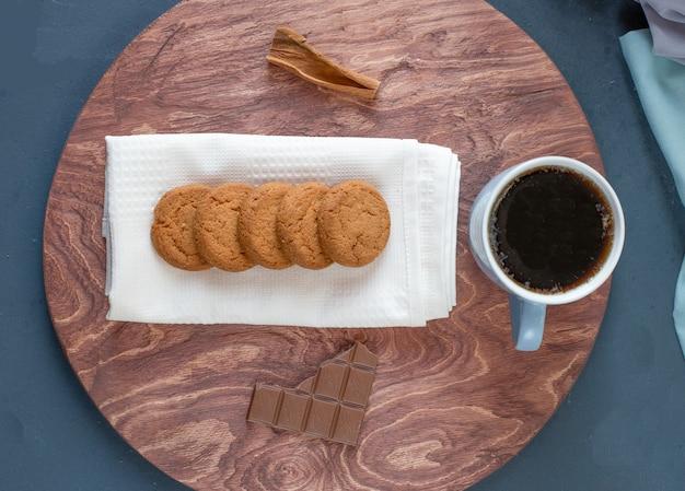 Ciasteczka owsiane, filiżanka herbaty i tabliczka czekolady na drewnianym talerzu.