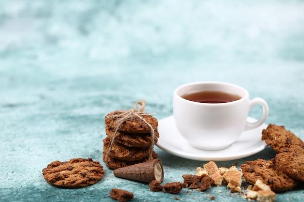 Ciasteczka owsiane i chrupki przy filiżance herbaty.