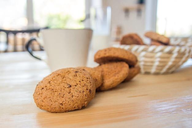 Ciasteczka owsiane i filiżankę herbaty na drewnianym stole.
