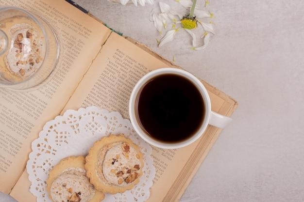 Ciasteczka owsiane i filiżankę herbaty na otwartej księdze.