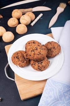 Ciasteczka owsiane i maślane z kawałkami czekolady na desce