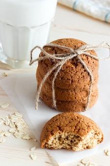 Ciasteczka owsiane i mleko w szkle, zdrowa przekąska. drewniane tło
