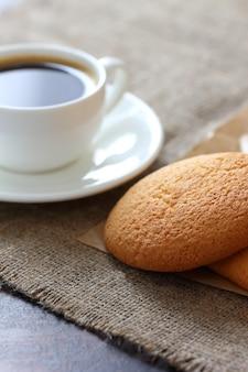Ciasteczka owsiane, kubek kawy i spodek na płótnie obrus.