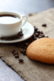 Ciasteczka owsiane, kubek z kawą i ziarnami kawy rozrzucone na płótnie obrus.