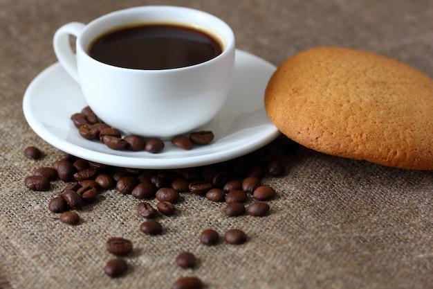 Ciasteczka owsiane, kubek z kawą, spodek i ziarna kawy rozrzucone na płótnie obrus.