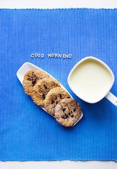 """Ciasteczka owsiane na białym talerzu z filiżanką mleka z napisem """"dzień dobry""""."""