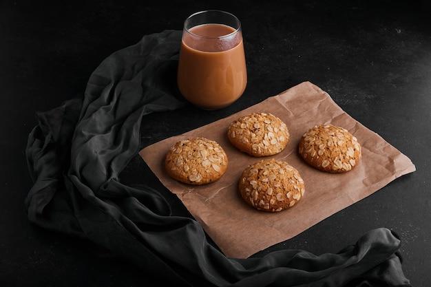 Ciasteczka owsiane na czarnej powierzchni ze szklanką gorącej czekolady.