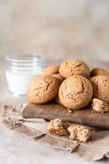 Ciasteczka owsiane na drewnianej desce do krojenia z filiżanką mleka zdrowa przekąska lub deser