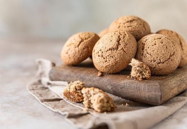 Ciasteczka owsiane na drewnianej deski do krojenia, brązowe tło betonu. zdrowa przekąska lub deser.