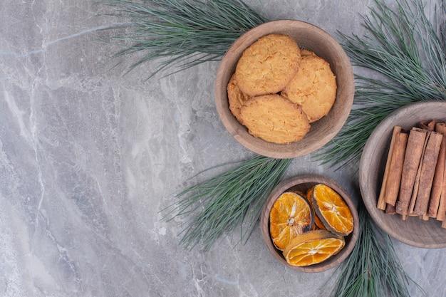 Ciasteczka owsiane na drewnianym kubku z plastrami cynamonu i pomarańczy