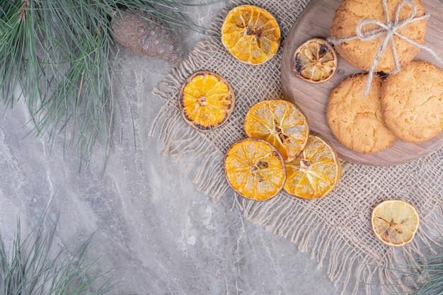 Ciasteczka owsiane na drewnianym talerzu otoczone suchymi plasterkami pomarańczy