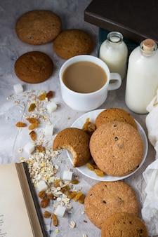 Ciasteczka owsiane o pracy ręcznej, książki, płatki owsiane, filiżanka kawy z mlekiem, rodzynki na lekkiej powierzchni. koncepcja śniadania