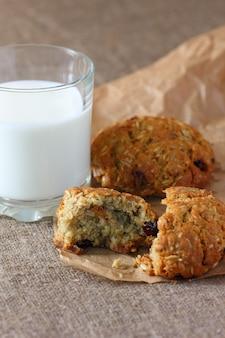 Ciasteczka owsiane połamane i szklanka mleka na papierze pakowym i na obrusie z płótna.