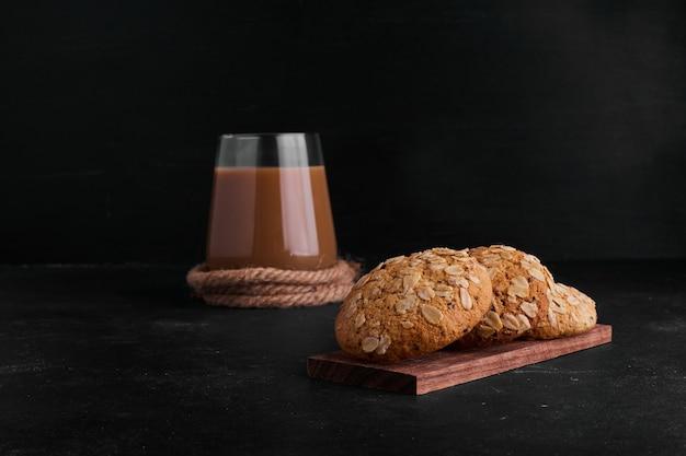 Ciasteczka owsiane z czarnuszką i szklanką kawy.