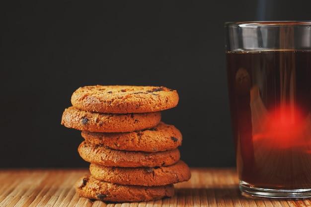 Ciasteczka owsiane z kawałkami czekolady i kubek aromatycznej czarnej herbaty