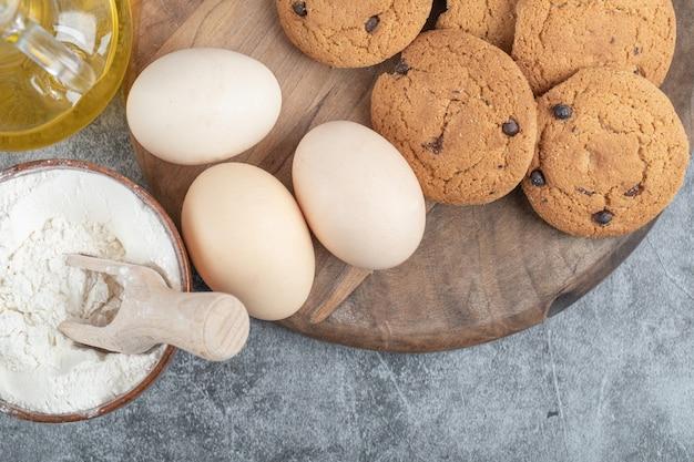 Ciasteczka owsiane z kroplami czekolady na drewnianej desce z dodatkami dookoła