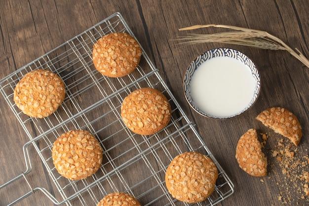 Ciasteczka owsiane z nasionami i zbożami w pobliżu miski mleka