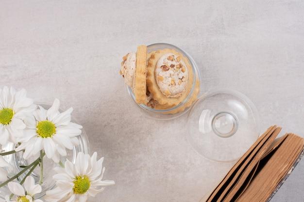 Ciasteczka owsiane z rodzynkami w szklanym słoju, książce i stokrotkach.
