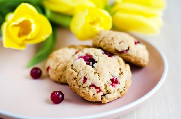Ciasteczka owsiane z żurawiną i płatkami, z żółtymi tulipanami. poranny bukiet i śniadanie, nieostrość