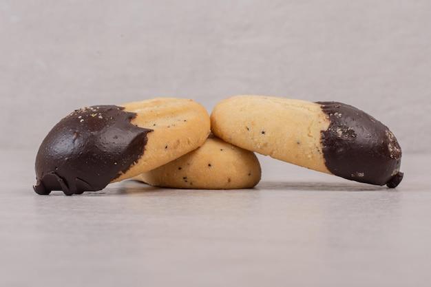 Ciasteczka ozdobione sosem czekoladowym na białej powierzchni.