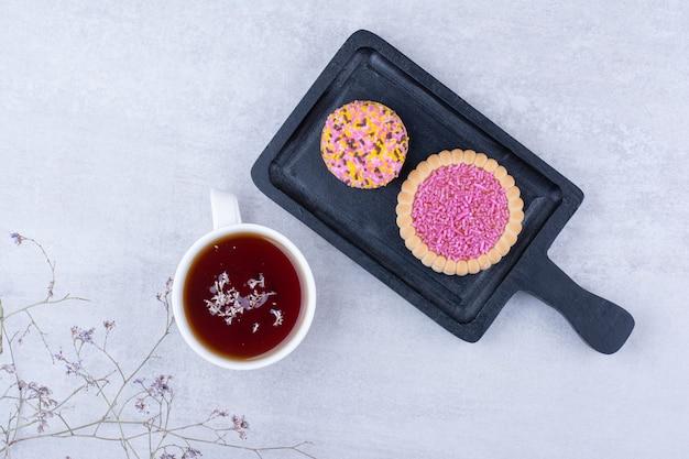 Ciasteczka ozdobione spryskiwaczami i filiżanką herbaty