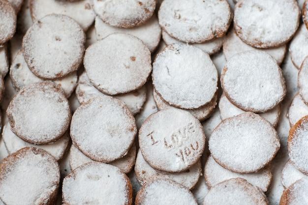 Ciasteczka piekarnicze z dekoracją cukru pudru. kocham cię napis