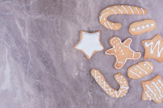 Ciasteczka piernikowe w kształcie kija, gwiazdy i owalu na marmurze