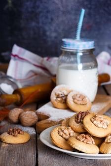 Ciasteczka piernikowe z orzechami włoskimi na stole i szklanka mleka