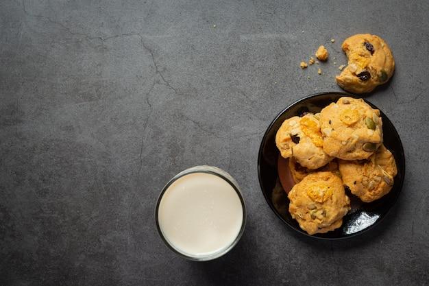 Ciasteczka podawane ze szklanką mleka na ciemnej podłodze