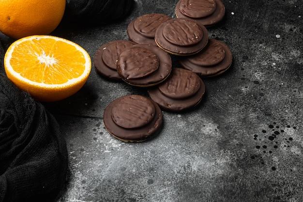 Ciasteczka pokryte czekoladą i wypełnione dżemem, na czarnym ciemnym tle kamiennego stołu, z miejscem na tekst