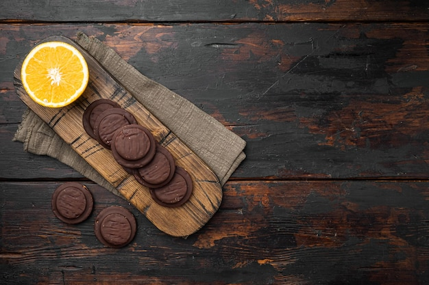 Ciasteczka pokryte czekoladą i wypełnione dżemem, na starym ciemnym tle drewnianego stołu, widok z góry płasko leżący, z miejscem na kopię na tekst
