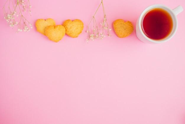 Ciasteczka serca z filiżanki herbaty i kwiaty