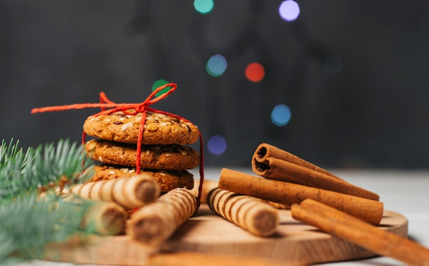 Ciasteczka, słodycze i laski cynamonu na tle lampek choinkowych.