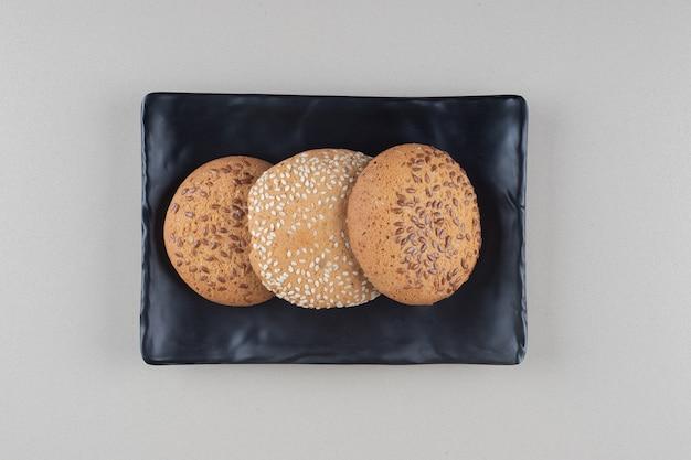 Ciasteczka spakowane na czarnym talerzu na marmurowym tle.