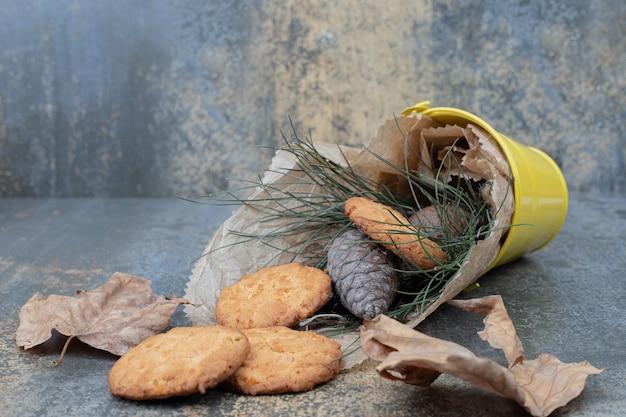 Ciasteczka, trawa i szyszki w wiadrze na marmurowym stole. wysokiej jakości zdjęcie