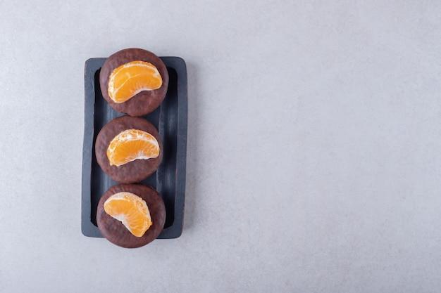 Ciasteczka w czekoladzie z plasterkiem mandarynki na drewnianej tacy, na marmurze.