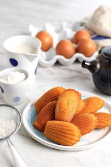 Ciasteczka w formie muszli - zbliżenie madeleine na desce na stole