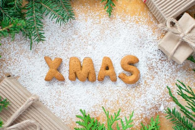 Ciasteczka w formie napisu xmas w postaci gwiazdek piernikowych ciasteczek na tle toczki z cukrem pudrem i ozdobami choinkowymi i choinką dookoła. koncepcja karty nowy rok
