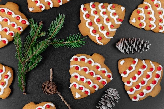 Ciasteczka w kształcie choinki z szyszek i gałęzi świerkowych na czarnym tle. koncepcja obchodów nowego roku