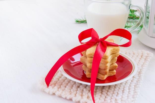 Ciasteczka w kształcie gwiazdek i mleka dla świętego mikołaja na białym tle
