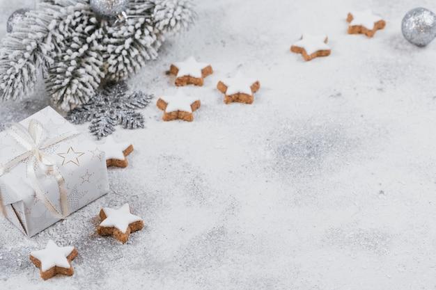 Ciasteczka w kształcie gwiazdy i ozdoby świąteczne na białym tle. koncepcja ferii zimowych.