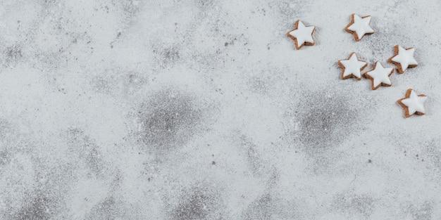 Ciasteczka w kształcie gwiazdy na białym tle. koncepcja ferii zimowych. widok z góry, wolne miejsce na tekst