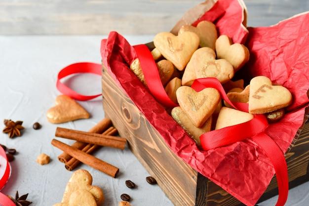 Ciasteczka w kształcie serc, na ciasteczkach litery love.decor czerwone wstążki. szczęśliwych walentynek