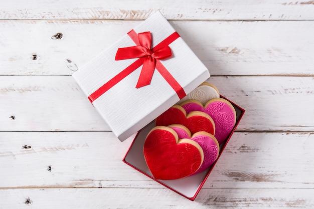 Ciasteczka w kształcie serca i róże na walentynki na białym drewnianym stole
