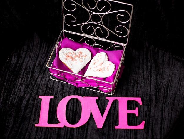 Ciasteczka w kształcie serca leżą w zbliżeniu trumny z miłością