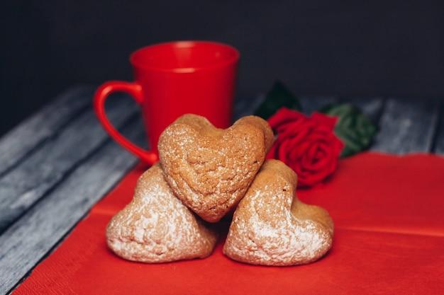 Ciasteczka w kształcie serca na czerwonej serwetce słodycze kwiat róży. wysokiej jakości zdjęcie