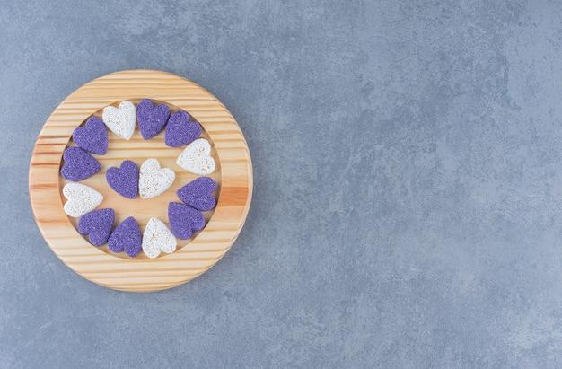 Ciasteczka w kształcie serca na talerzu, na marmurowym tle.